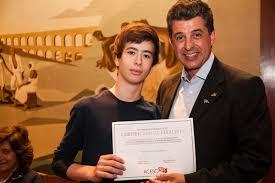 O aluno Allan Catach recebendo o certificado do concurso literário da ACESC